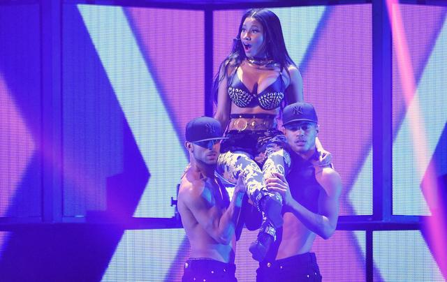 Nicki Minaj being held up by two men